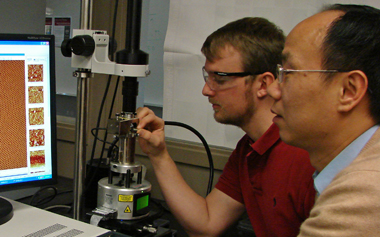 Chuanbing Tang (right) and Christopher Hardy used atomic force microscopy to characterize the nanoscale patterns they built from the bottom up.