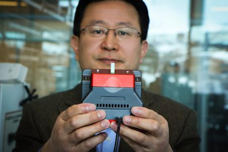 University of Utah materials science and engineering professor Ling Zang holds up a prototype handheld detector his company is producing that can sense explosive materials and toxic gases. His research team developed a new material for the detector that can sense alkane fuel, a key ingredient in such combustibles as gasoline, airplane fuel and homemade bombs. Photo credit: Dan Hixson/University of Utah College of Engineering