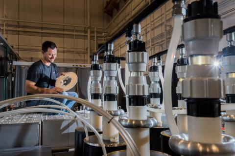 Sandia National Laboratories technologist Joshua Usher loads a target into the main power flow section of Veloce, a Sandia pulsed-power generator. The machine uses pressure rather than chemicals to form nanocomponents from nanoparticles. Photo by Randy Montoya